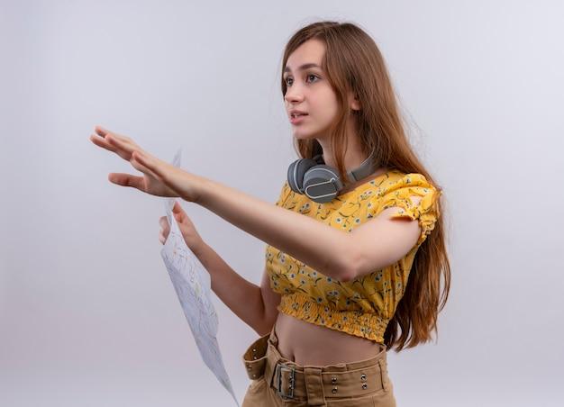 Verward jong meisje dat een koptelefoon op de nek draagt en kaart houdt die de hand uitrekt en naar de linkerkant op geïsoleerde witte ruimte kijkt