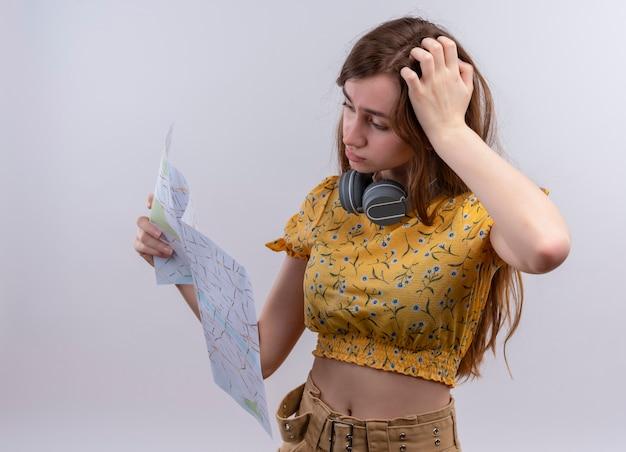 Verward jong meisje dat een koptelefoon op de nek draagt en kaart houdt en ernaar kijkt op geïsoleerde witte ruimte