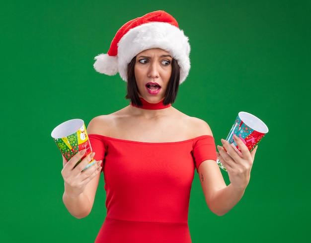 Verward jong meisje dat santahoed draagt die plastic kerstmiskoppen bekijkt die één geïsoleerd op groene muur bekijken