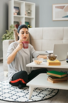 Verward jong meisje gebruikte laptop met kopje thee zittend op de vloer achter de salontafel in de woonkamer