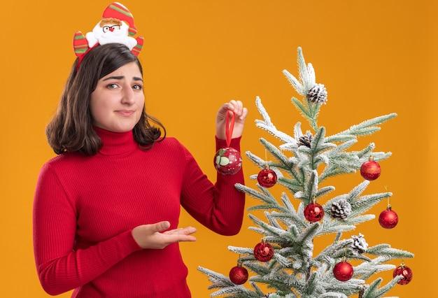 Verward jong meisje in kerstmissweater die grappige hoofdband naast een kerstboom over oranje achtergrond draagt