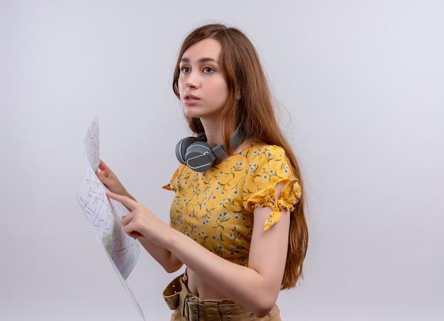 Verward jong meisje met een koptelefoon op de nek en kaart te houden en erop te wijzen op geïsoleerde witte ruimte met kopie ruimte