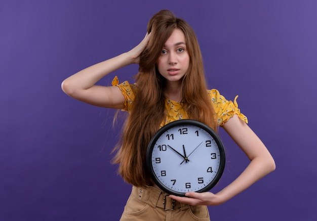 Verward jong meisje met klok en hand op het hoofd zetten op geïsoleerde paarse ruimte