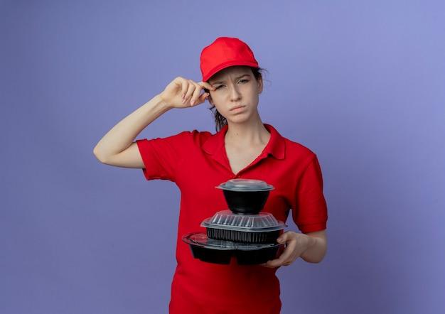 Verward jong mooi bezorgmeisje dat rode uniform en pet draagt die voedselcontainers houdt die oog aanraken dat op purpere achtergrond met exemplaarruimte wordt geïsoleerd