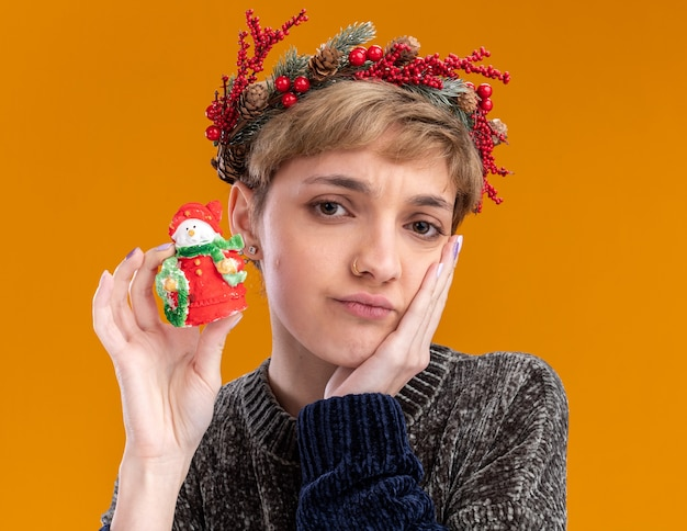 Verward jong mooi meisje dat de hoofdkroon van kerstmis draagt die het kleine standbeeld van de kerstmissneeuwman houdt die hand op gezicht houdt die camera bekijkt die op oranje achtergrond wordt geïsoleerd