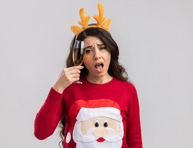 Verward jong mooi meisje dragen rendiergeweien hoofdband en santa claus trui houden glas champagne hoofd aanraken met het kijken