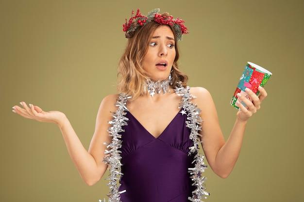 Verward jong mooi meisje, gekleed in paarse jurk en krans met bloemenslinger op nek met kerstbeker spreidende handen geïsoleerd op olijfgroene achtergrond