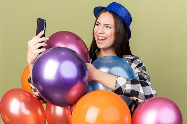 Verward jong mooi meisje met een blauwe hoed die achter ballonnen staat en naar een telefoon kijkt die op een olijfgroene muur is geïsoleerd