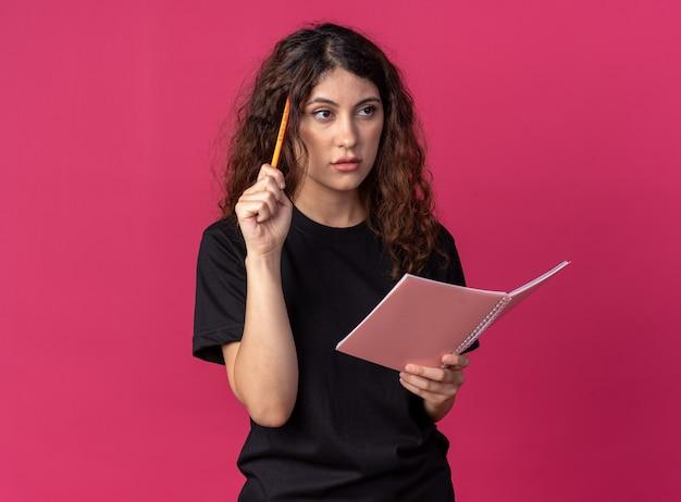 Verward jong mooi meisje met potlood en notitieboekje dat een gebaar naar de zijkant kijkt