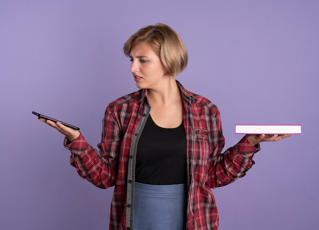 Verward jong slavisch studentenmeisje houdt telefoon en boek vast