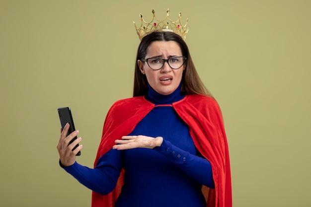 Verward jong superheld meisje bril en kroon houden en punten met hand op telefoon geïsoleerd op olijfgroene achtergrond