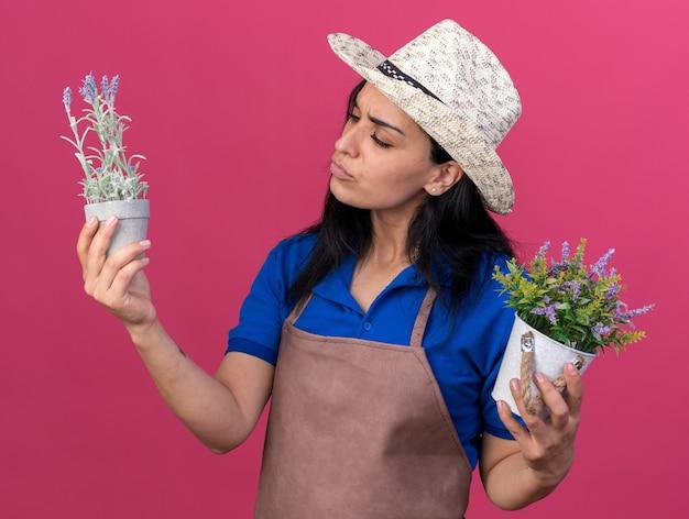 Verward jong tuinmanmeisje dat uniform en hoed draagt en naar bloempotten kijkt die op roze muur zijn geïsoleerd