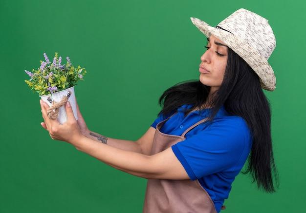 Verward jong tuinmanmeisje met uniform en hoed in profielweergave, vasthoudend en kijkend naar bloempot geïsoleerd op groene muur