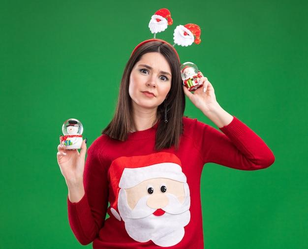 Verward jong vrij kaukasisch meisje dat de kerstman-trui en hoofdband draagt die de kerstman en sneeuwmanbeeldjes met grote ogen houdt die op groene muur worden geïsoleerd