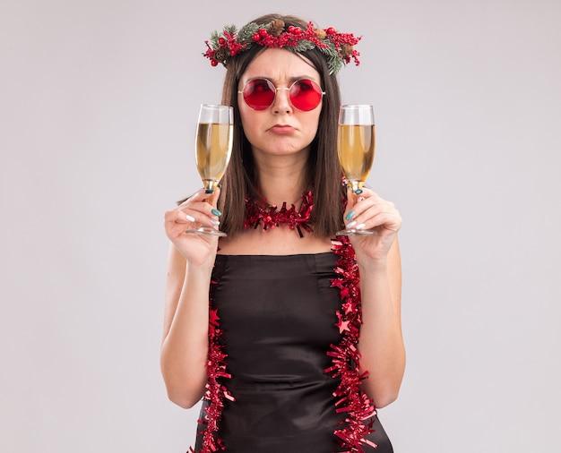 Verward jong vrij kaukasisch meisje die kerstmis hoofdkroon en klatergoudslinger dragen rond hals met glazen die twee glazen champagne houden