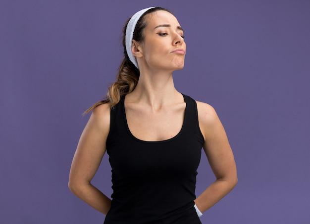 Verward jong, vrij sportief meisje met een hoofdband en polsbandjes die de handen achter de rug houden en naar beneden kijken