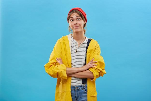 Verward jong wijfje dat vrijetijdskleding draagt die zich gekruiste handen bevindt die over blauwe muur worden geïsoleerd. verraste vrouw die met afgeluisterde ogen kijkt die haar relaties met echtgenoot sorteren