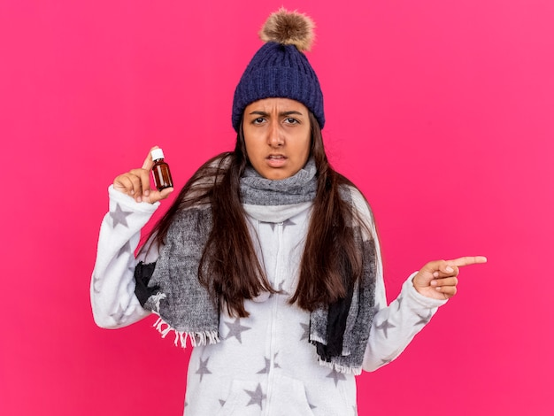 Verward jong ziek meisje dat de winterhoed met sjaal draagt die geneeskunde in glasfles houdt punten aan kant die op roze achtergrond met exemplaarruimte wordt geïsoleerd