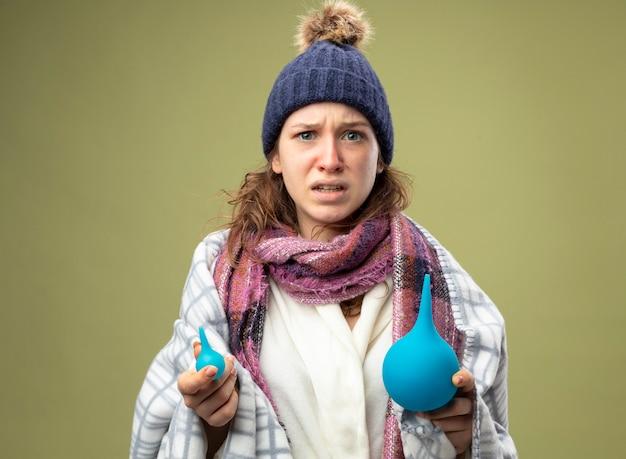 Verward jong ziek meisje dat een wit gewaad en een wintermuts met een sjaal draagt die in geruite klysma's wordt verpakt die op olijfgroen worden geïsoleerd