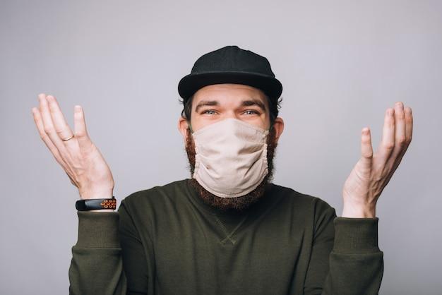 Verward jonge bebaarde hipster man gebaren en anti covid masker dragen