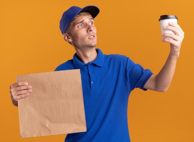 Verward jonge blonde bezorger houdt papieren pakket en kijkt naar beker op oranje