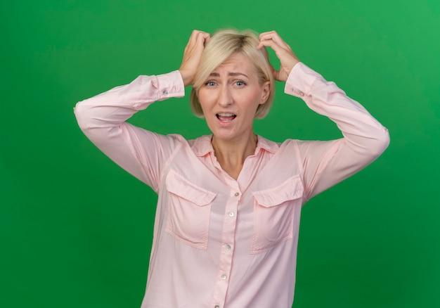 Verward jonge blonde slavische vrouw hoofd met handen aan te raken geïsoleerd op groene achtergrond