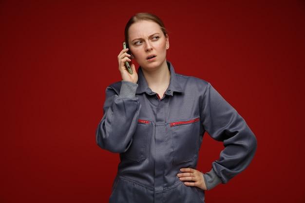Verward jonge blonde vrouwelijke ingenieur dragen uniform praten over telefoon houden hand op taille kijken kant