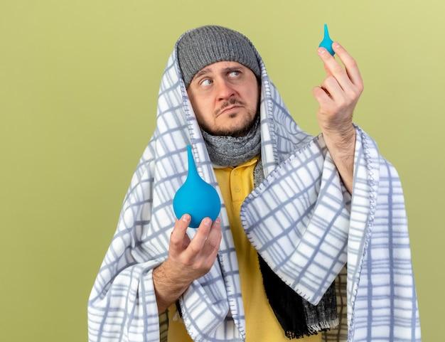 Verward jonge blonde zieke slavische man met muts en sjaal gewikkeld in plaid kijkt klysma's geïsoleerd op olijfgroene muur met kopie ruimte
