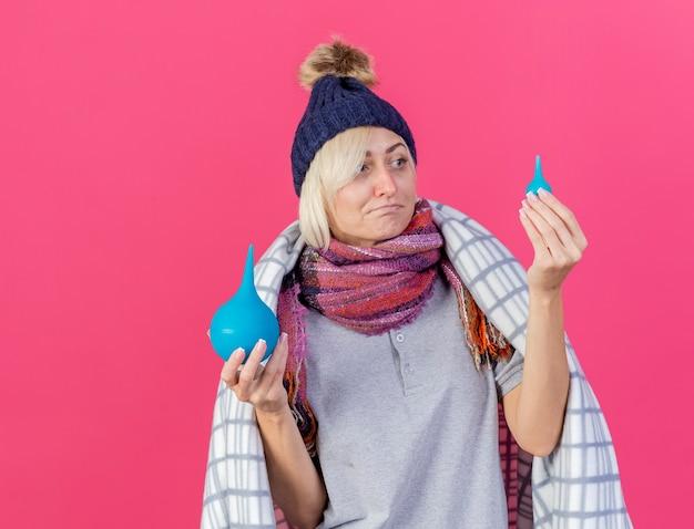 Verward jonge blonde zieke slavische vrouw met winter muts en sjaal gewikkeld in geruite ruimen en kijkt naar klysma's geïsoleerd op roze muur met kopie ruimte