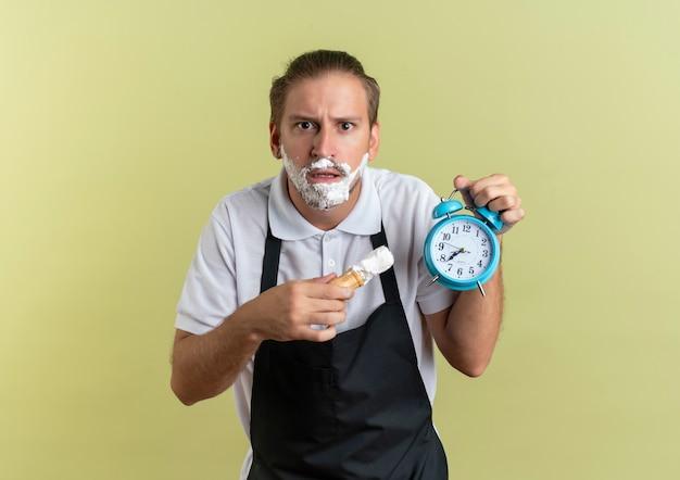 Verward jonge knappe kapper bedrijf wekker en scheerkwast met scheerschuim op zijn gezicht geïsoleerd op olijfgroen met kopie ruimte