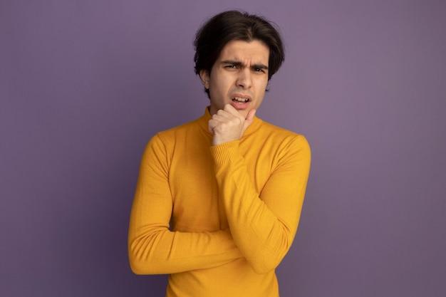 Verward jonge knappe kerel die gele coltrui draagt ?? die hand onder kin zet die op purpere muur wordt geïsoleerd