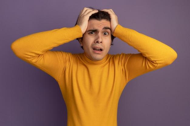 Verward jonge knappe man met gele coltrui greep hoofd geïsoleerd op paarse muur