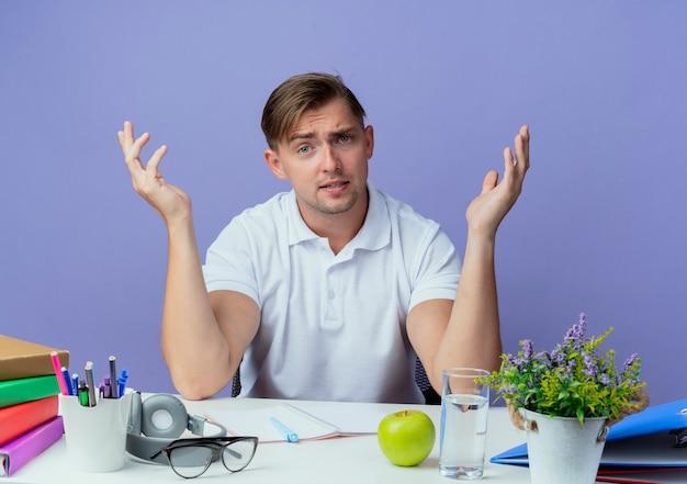 Verward jonge knappe mannelijke student zittend aan een bureau met hulpmiddelen van de school spreidt handen