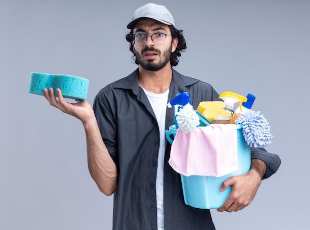 Verward jonge knappe schoonmaakster die t-shirt en pet draagt ?? die emmer met schoonmaakgereedschap en spons houdt die op een witte muur wordt geïsoleerd