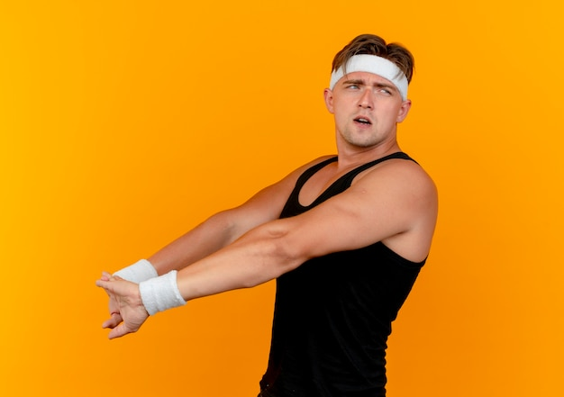 Verward jonge knappe sportieve man met hoofdband en polsbandjes permanent in profiel te bekijken kant kijken en strekken handen geïsoleerd op oranje