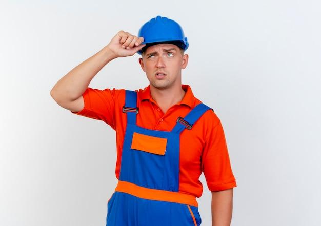 Verward jonge mannelijke bouwer dragen uniform en veiligheidshelm hand zetten helm