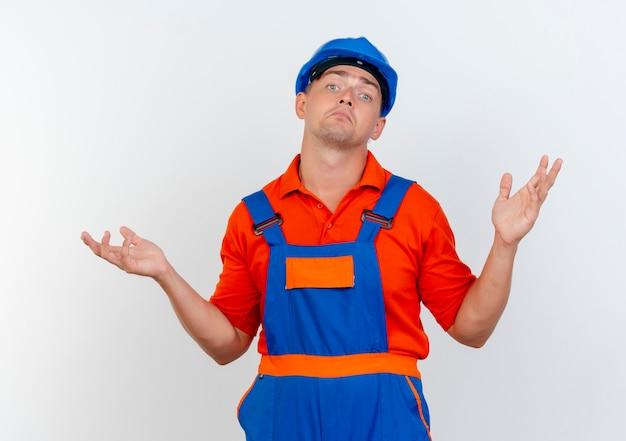 Verward jonge mannelijke bouwer uniform dragen en veiligheidshelm spreidt handen