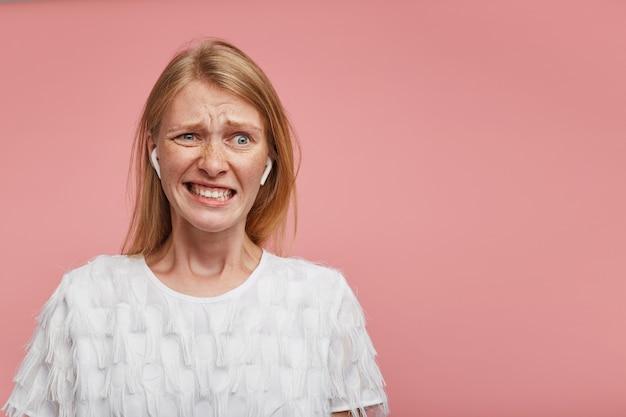 Verward jonge mooie roodharige vrouw fronst haar gezicht en toont tanden terwijl ze grimassen haar gezicht, draagt een wit feestelijk t-shirt terwijl ze over roze achtergrond staat