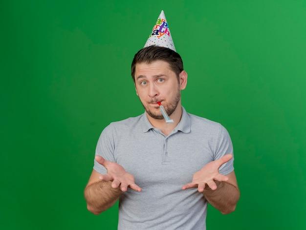 Verward jonge partij kerel dragen verjaardag glb blazen fluitje en spreidende handen geïsoleerd op groen