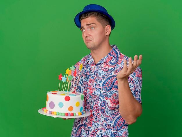 Verward jonge partij kerel kijken naar kant dragen blauwe hoed met cake en spreidende hand geïsoleerd op groen