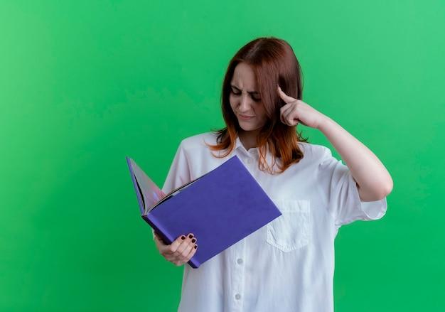 Verward jonge roodharige meisje houden en kijken naar map en vinger op het hoofd zetten geïsoleerd op groene achtergrond met kopie ruimte