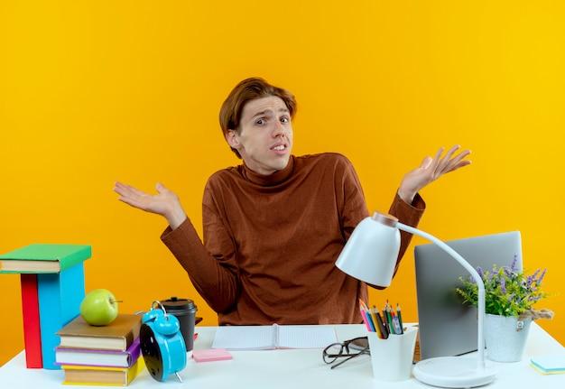Verward jonge student jongen zittend aan een bureau met hulpmiddelen van de school spreidt handen