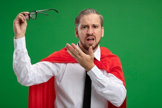 Verward jonge superheld man met stropdas bedrijf en punten met de hand op glazen geïsoleerd op groen