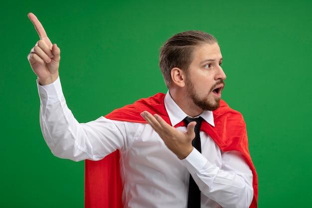 Verward jonge superheld man met stropdas en punten aan de zijkant geïsoleerd op groen