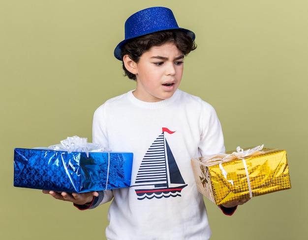 Verward jongetje met een blauwe feestmuts die geschenkdozen vasthoudt en bekijkt