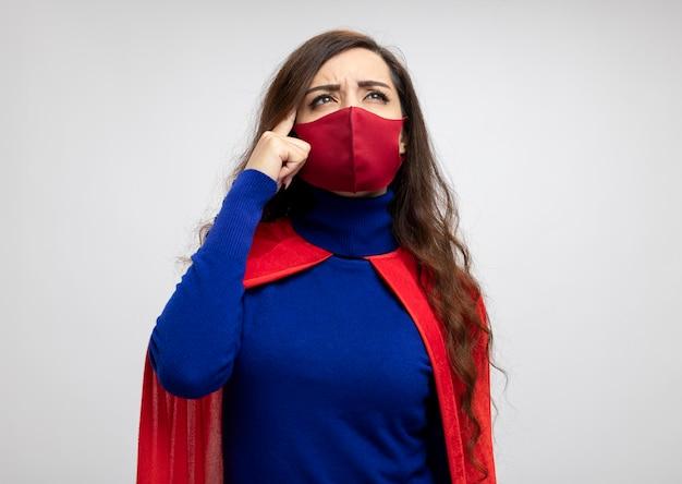 Verward kaukasisch superheldmeisje met rode cape die rood beschermend masker draagt
