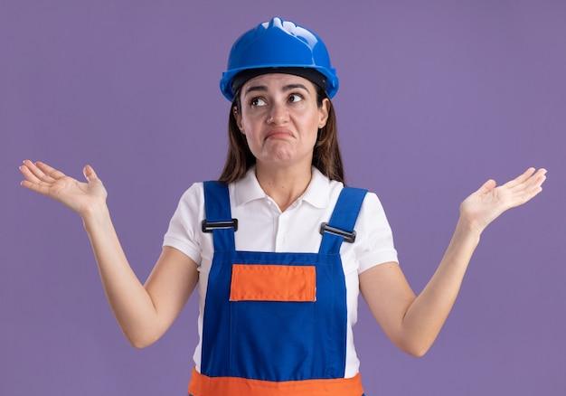 Verward kijken naar jonge bouwersvrouw aan de zijkant in uniforme spreidende handen die op paarse muur worden geïsoleerd