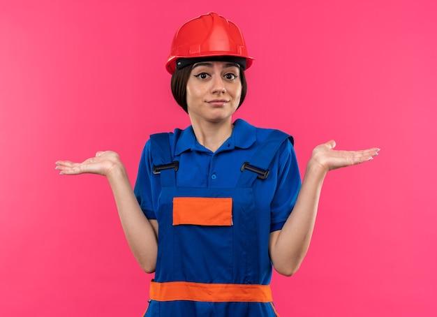 Verward kijkend naar de jonge bouwvrouw aan de zijkant in uniform spreidende handen geïsoleerd op roze muur