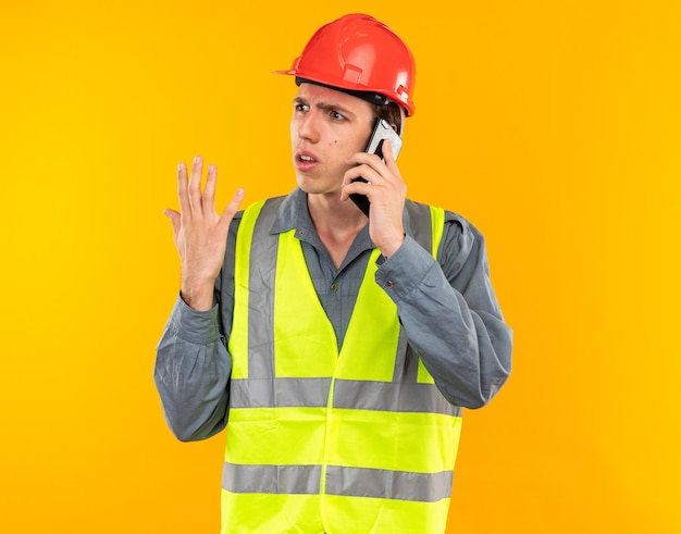 Verward kijkend naar de kant van de jonge bouwvakker in uniform spreekt aan de telefoon