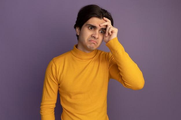 Verward kijkend naar kant jonge knappe kerel die gele coltrui draagt ?? die hand op tempel zet die op purpere muur wordt geïsoleerd
